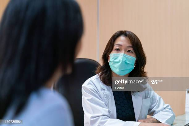 Mature doctor listening to female patient. Healthcare worker is looking at woman. Medical professional is wearing surgical mask in clinic.